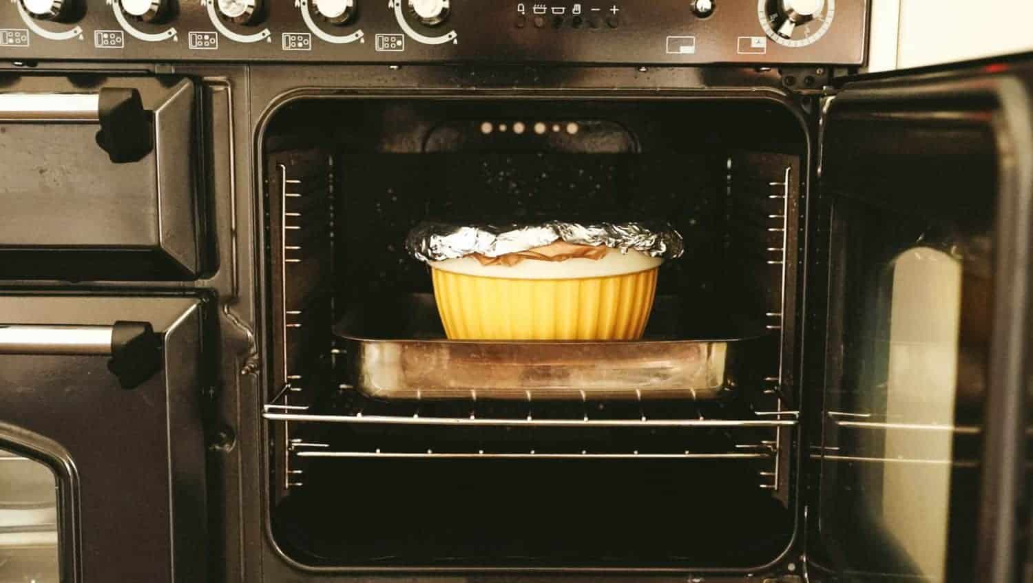An oven with the door open and a roasting tin and pudding bowl on the oven shelf.