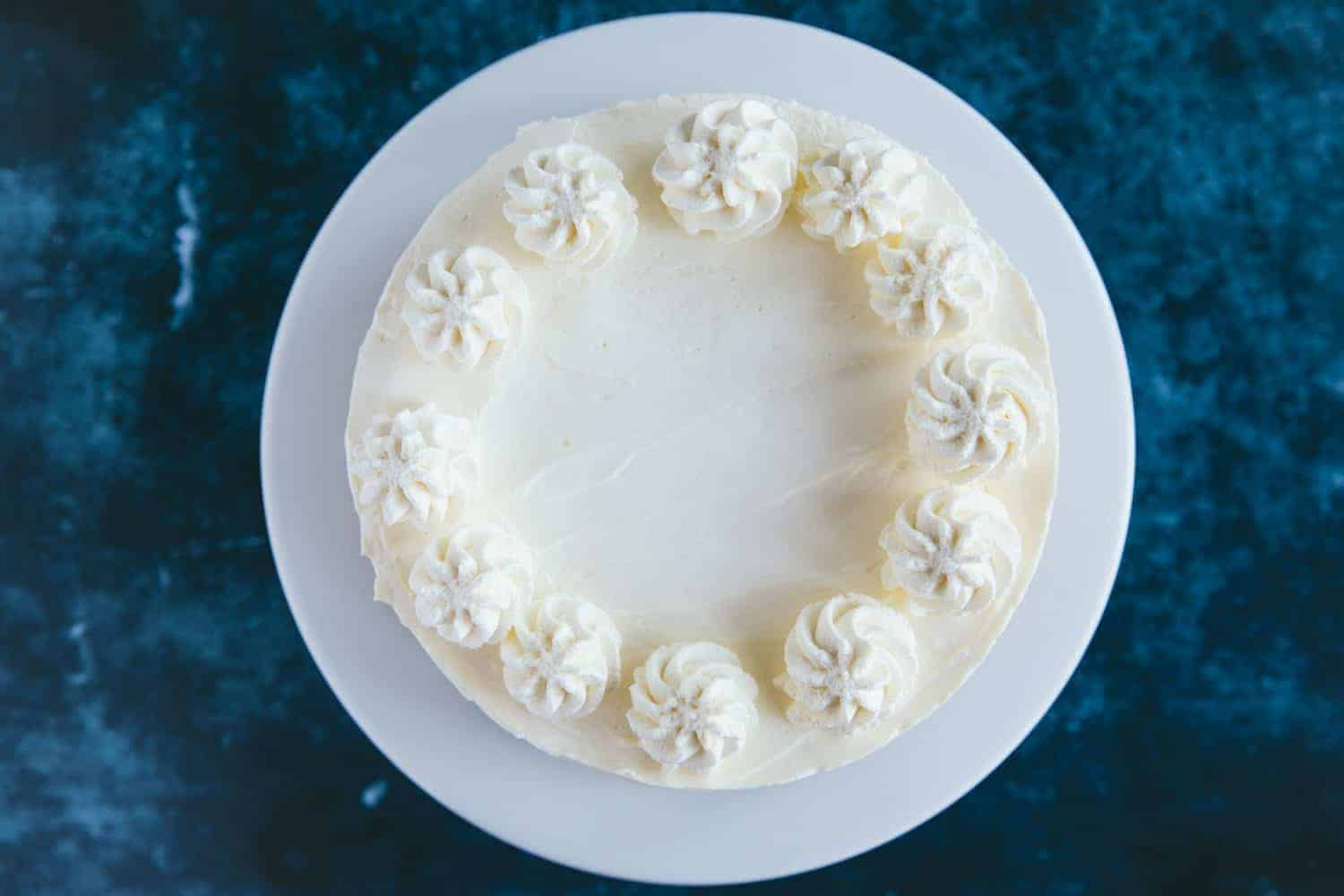 A cheesecake with swirls of piped cream on top.
