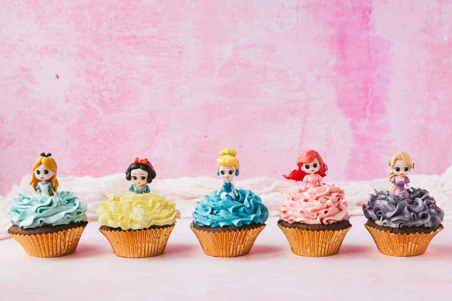 A row of Disney Princess Cupcakes. Alice in Wonderland, Snow White, Cinderella, Ariel and Rapunzel with coloured frosting.