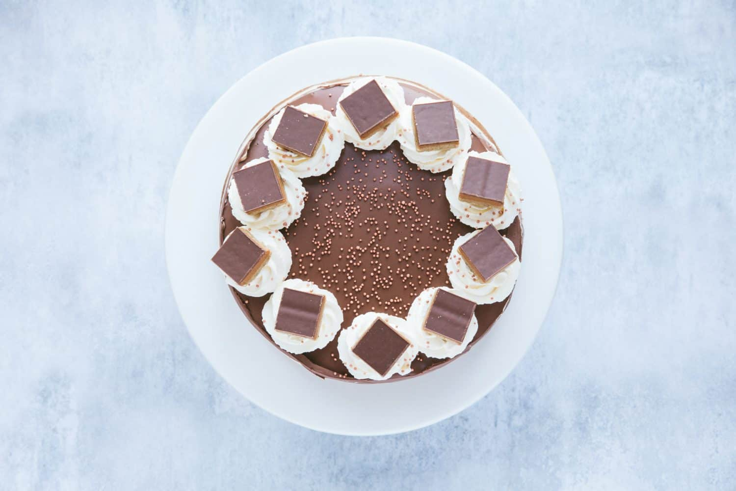 A cheesecake with chocolate toppings and gold coloured sprinkles.