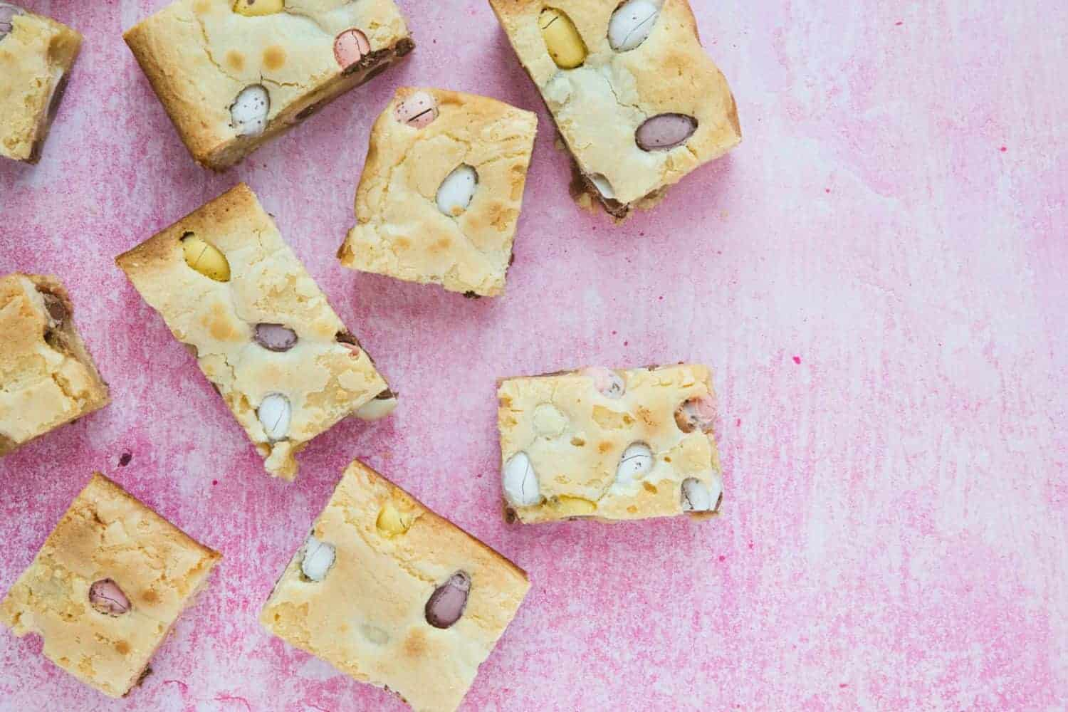 Slices of blondie on a pink background.