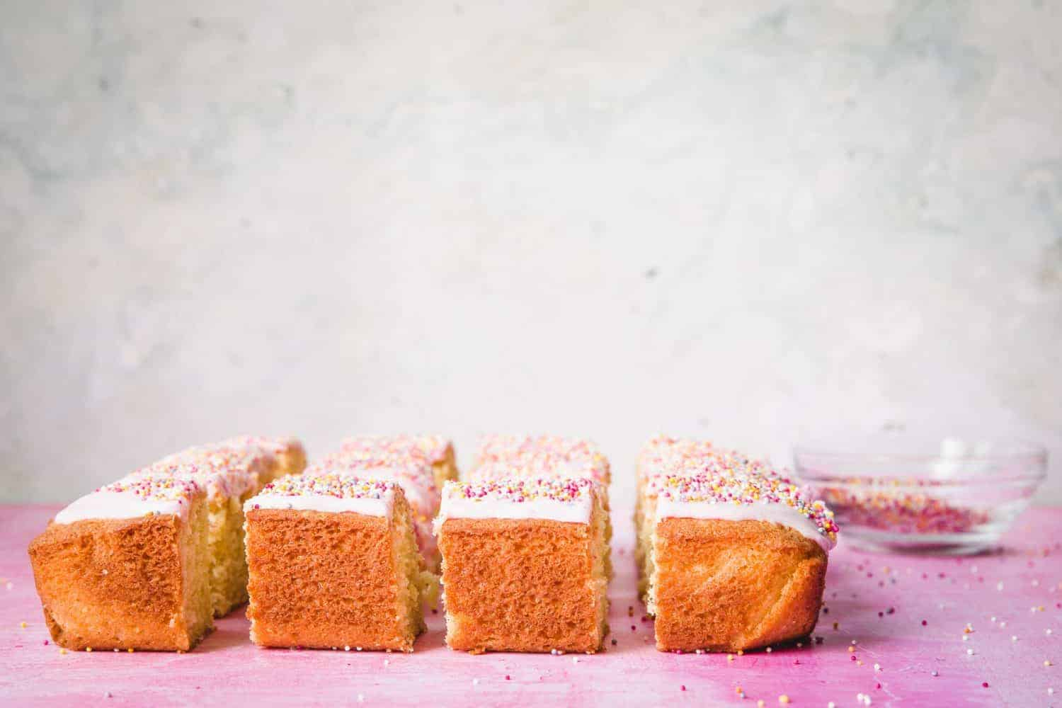 Squares of school cake on a pink surface.