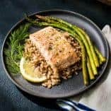 Lemon dill salmon and asparagus plated with farro on a gray plate.