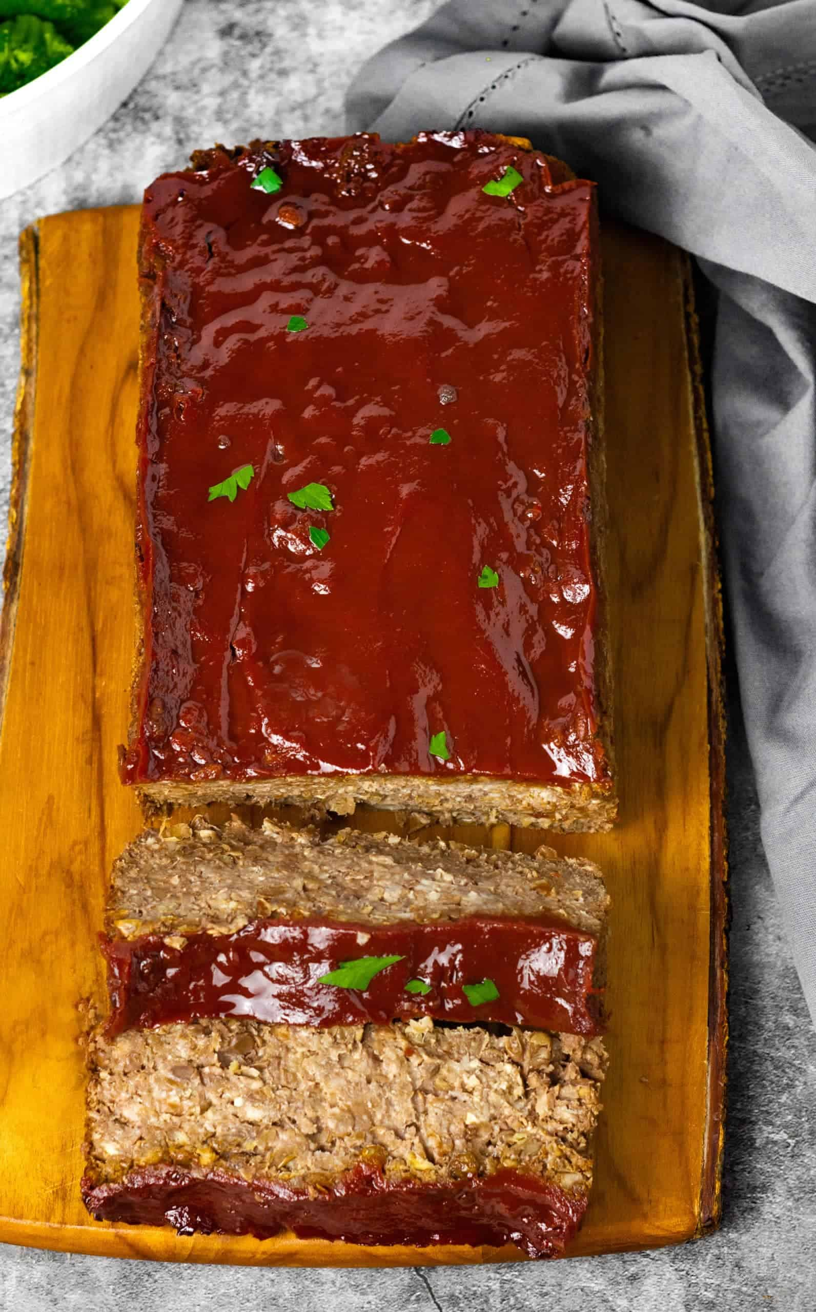 Overlay of vegan lentil loaf on a wooden cutting board with grey napkin on a grey background