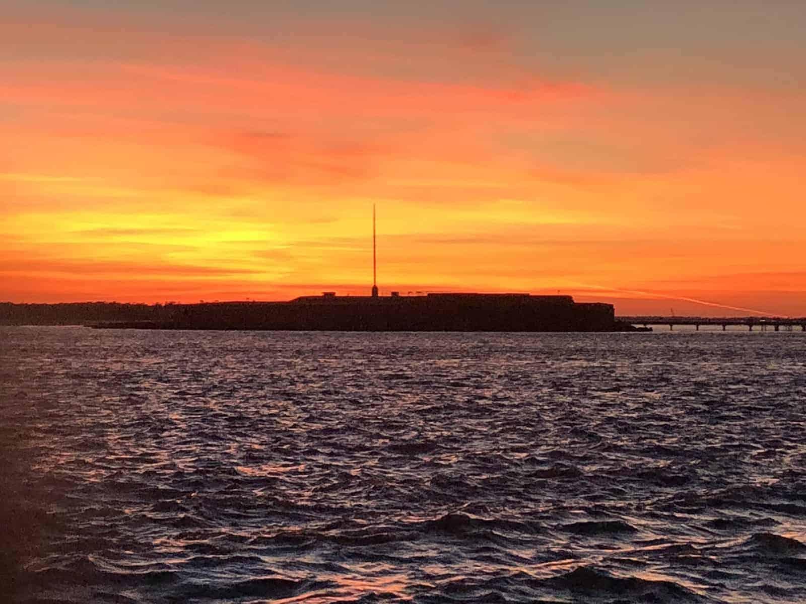 Orange skyline over the horizon. Sunset cruise Charleston, SC