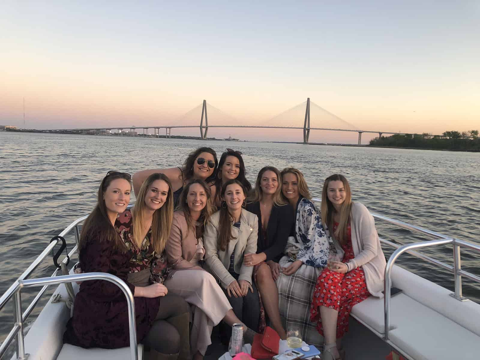 Group of women in front of sunset and bridge. Sunset cocktail cruise Charleston, SC