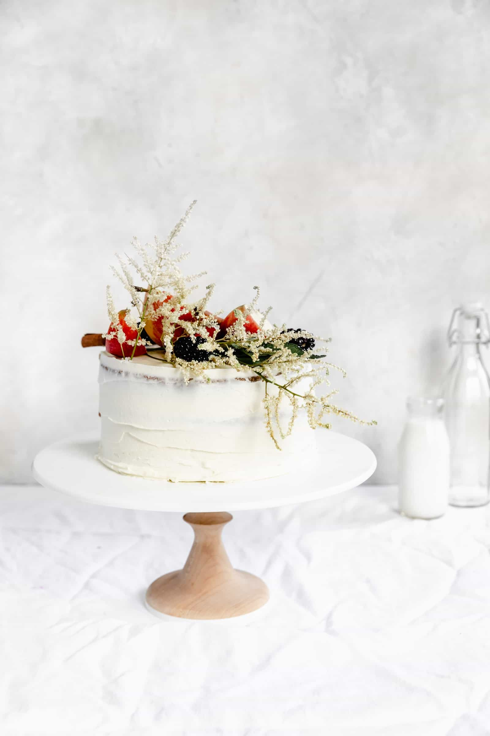 caramel apple cake witih fall flowers on a cake stand