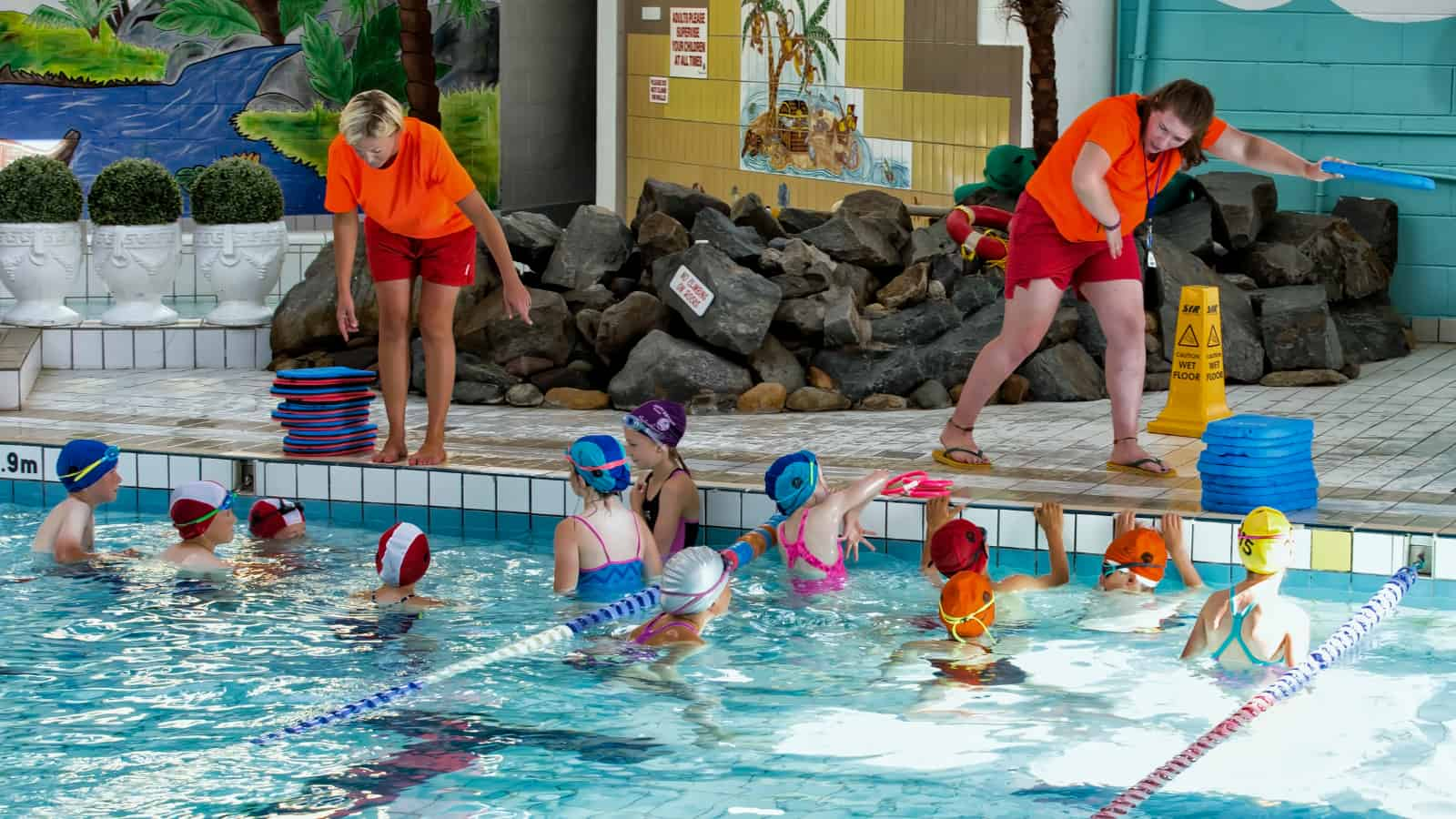 Swimming Instructor teaching a group of children to swim during swimming Lessons