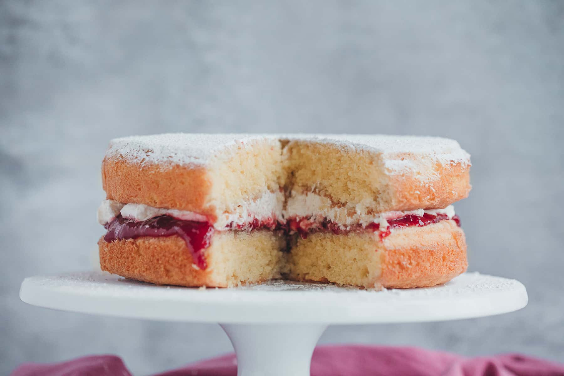 A Victoria Sandwich cake that has been sliced open. There is a cream and jam filling.