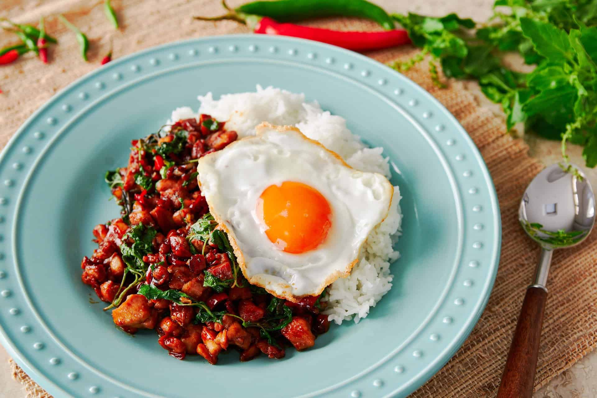 Basil Chicken or Pad Kraprow Gai is a classic Thai street food that can be thrown together at home in a matter of minutes. With spicy, garlic infused chicken and basil on Jasmine rice, the dish is topped off with a Thai-style fried egg.