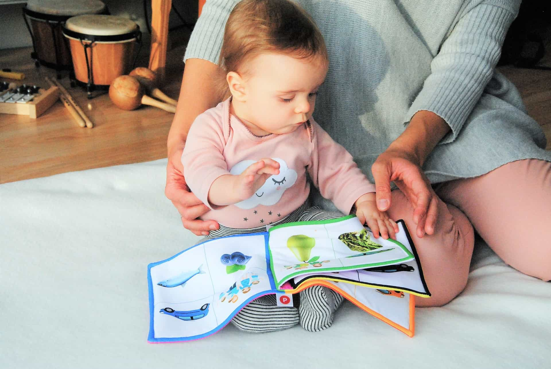 Stay at home mum with baby looking through a book