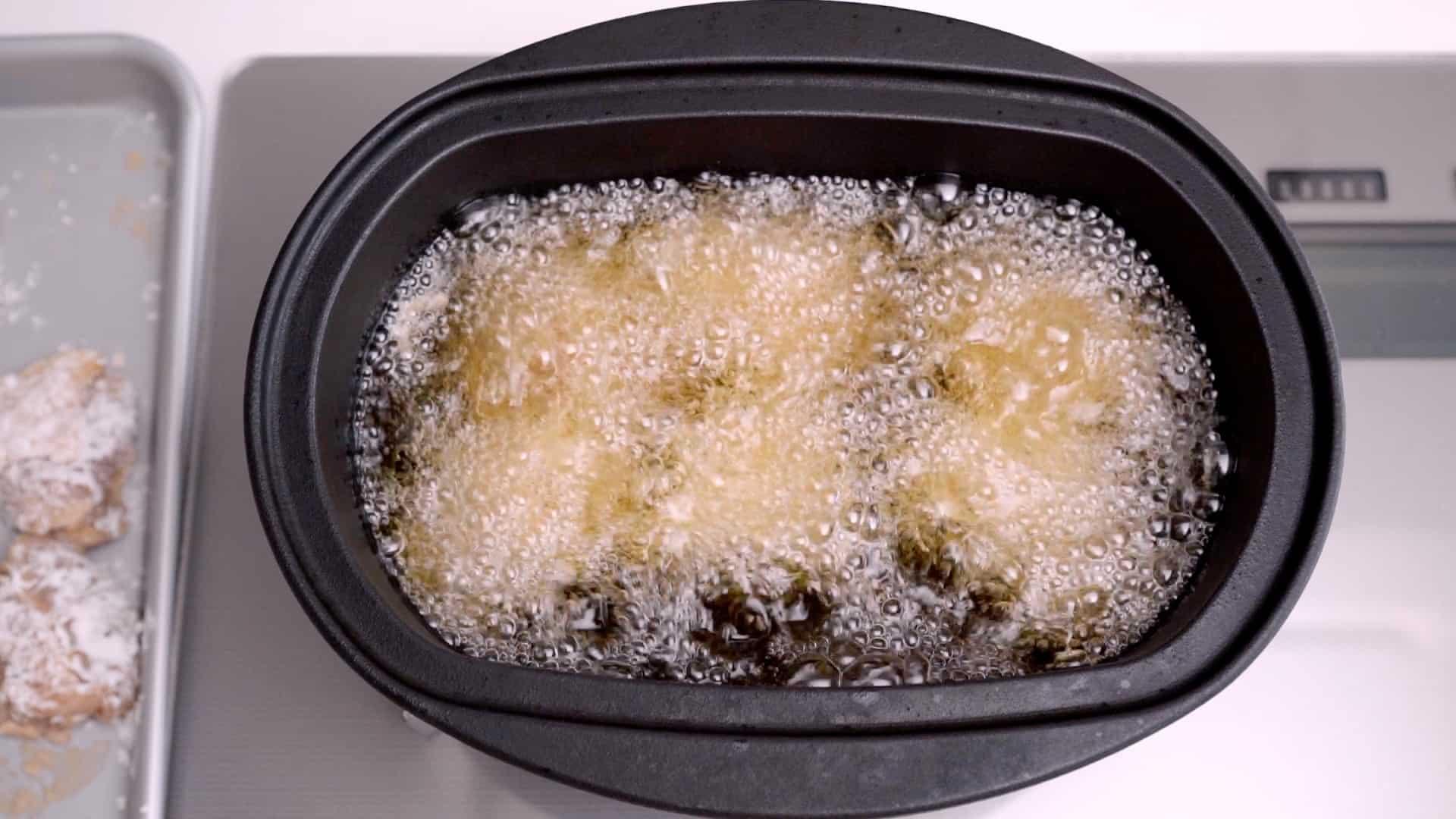 Karaage frying in oil in a cast iron pot.