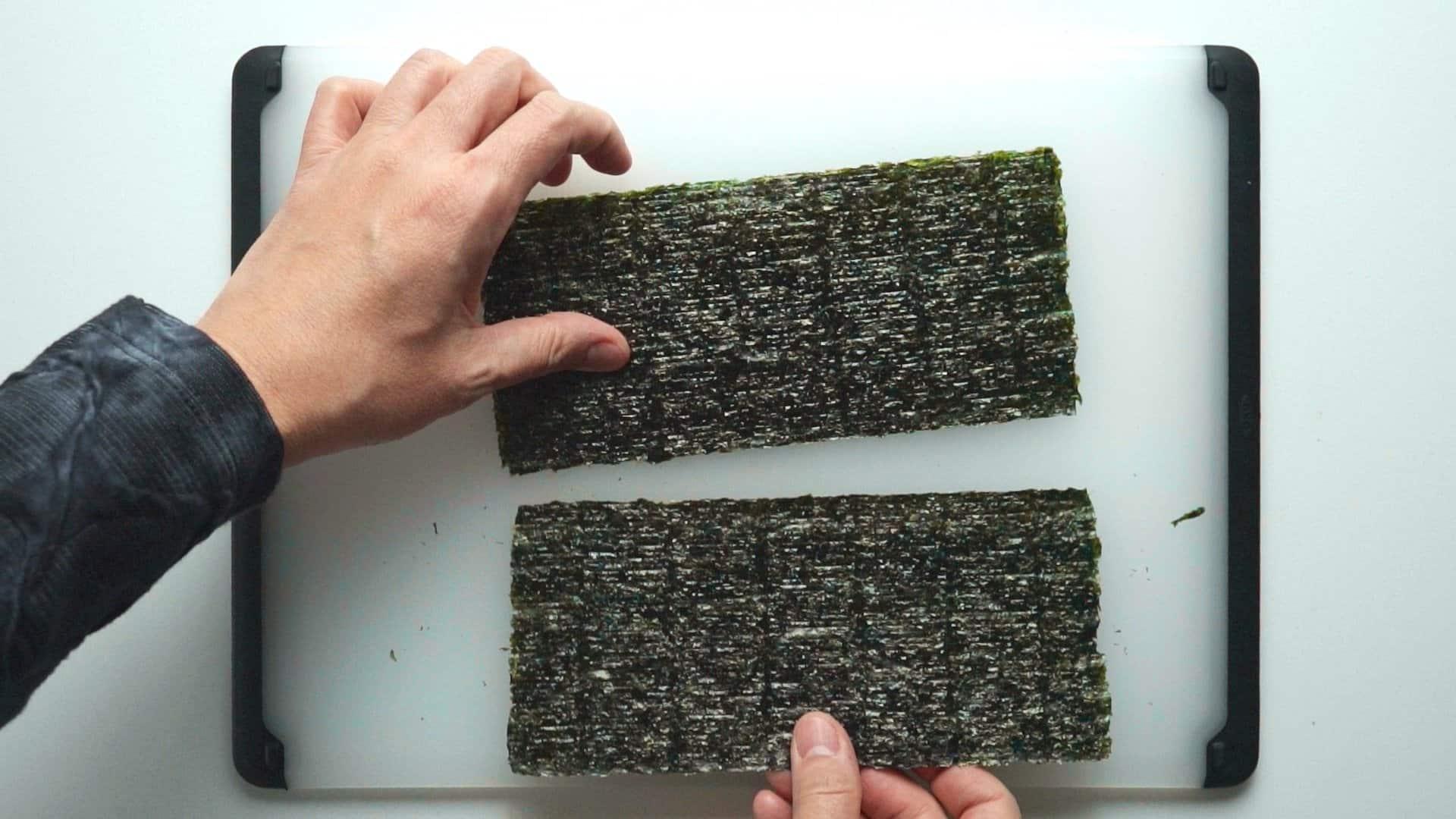 Cutting sheet of nori in half.