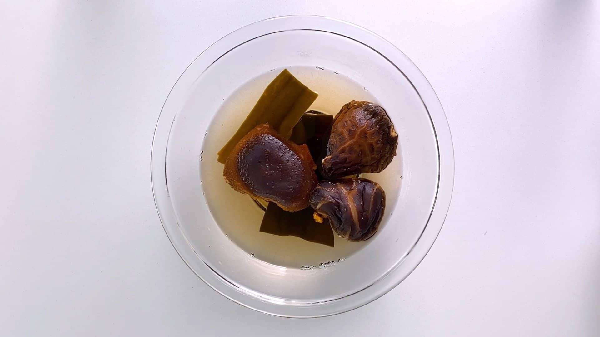 Rehydrating shiitake mushrooms and konbu to make vegan dashi stock.
