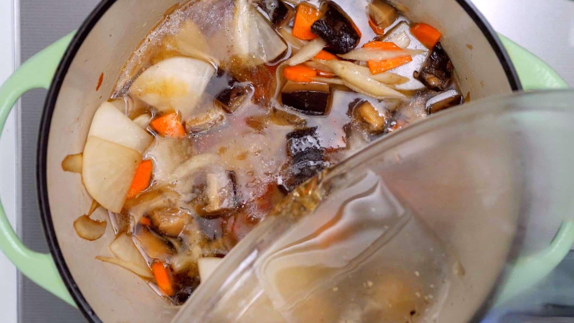 Adding shiitake dashi to vegan Japanese soup.