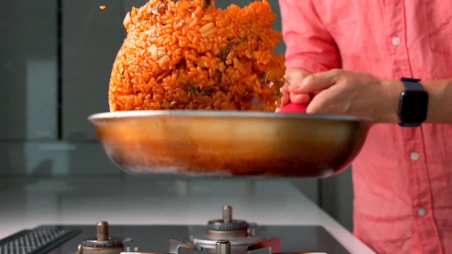 Tossing kimchi fried rice in a frying pan.