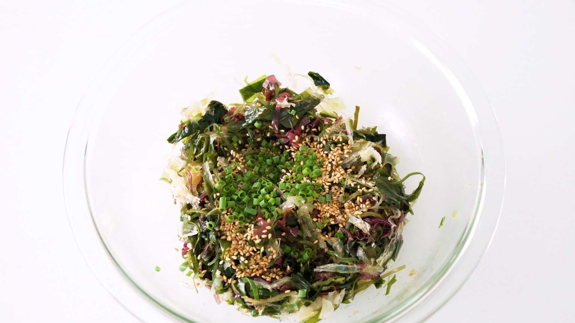 Seaweed salad mixed together with dress, sesame seeds and scallions in a glass bowl.