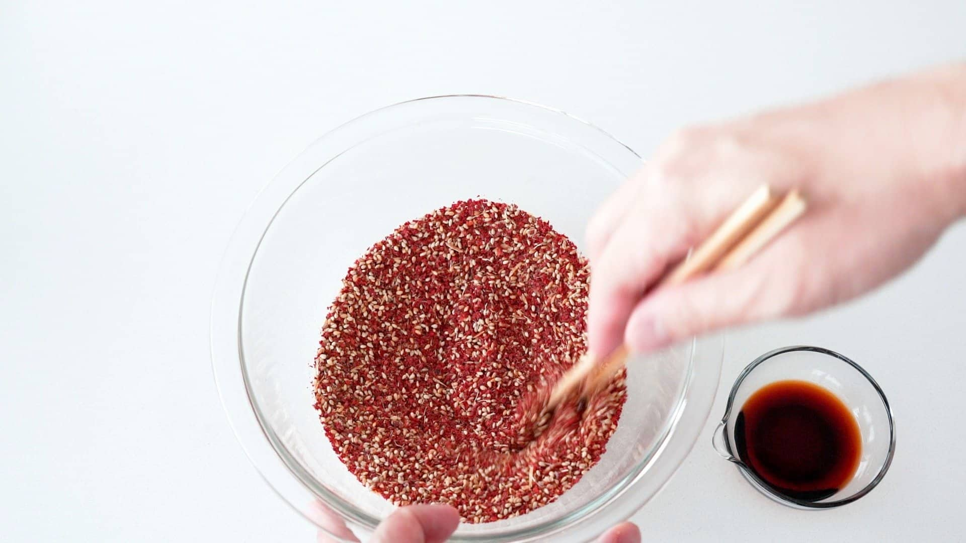 Mixing chili flakes, sesame seeds and spices together in a glass bowl for making chili oil