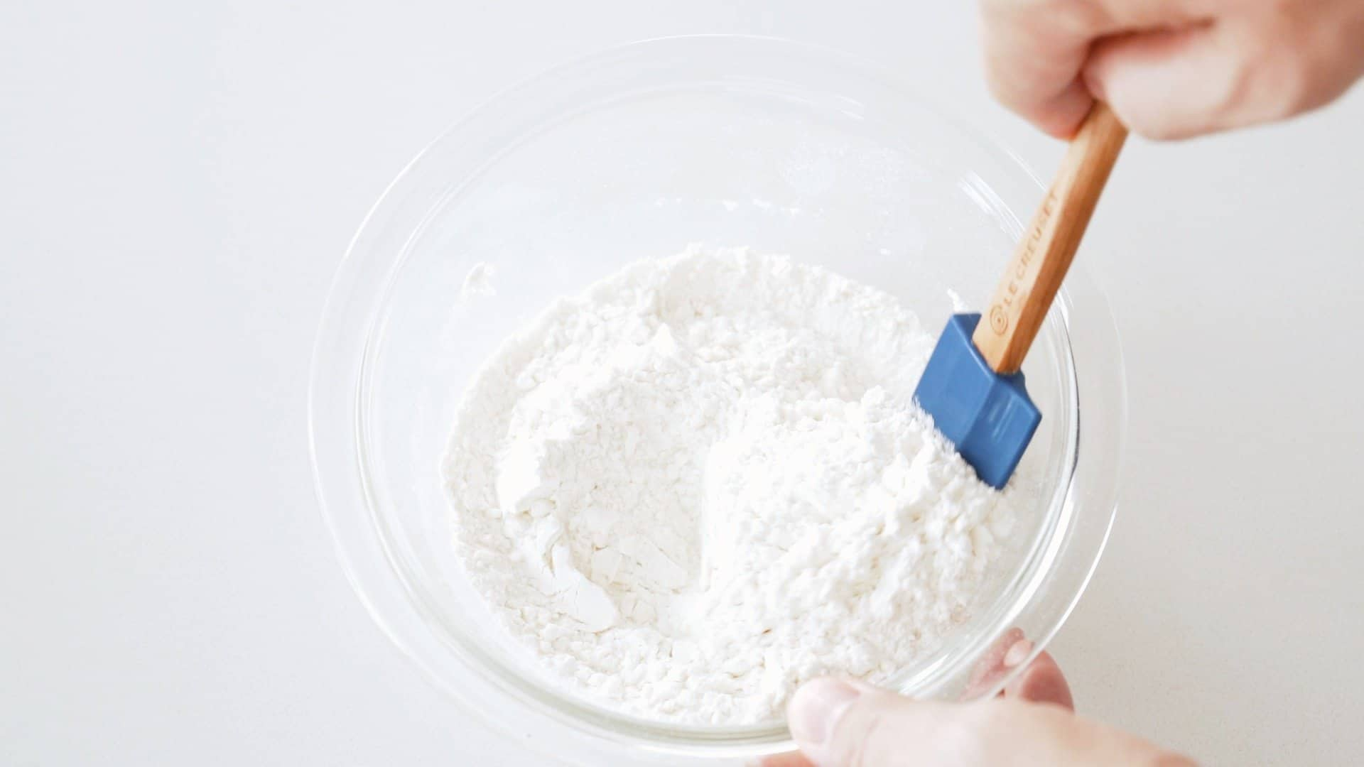 Mixing flour and salt in a glass bowl for making Hungarian Dumplings.
