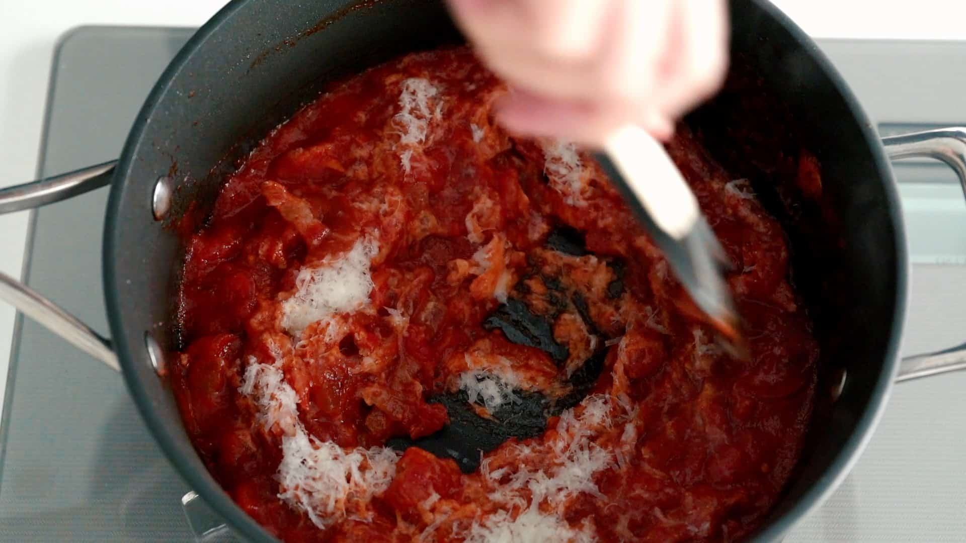 Stirring grated Pecorino Romano cheese into Amatriciana Sauce.