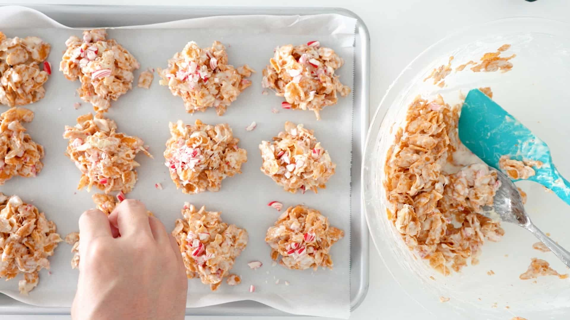 Topping crispy peppermint bark with crushed candy cane.