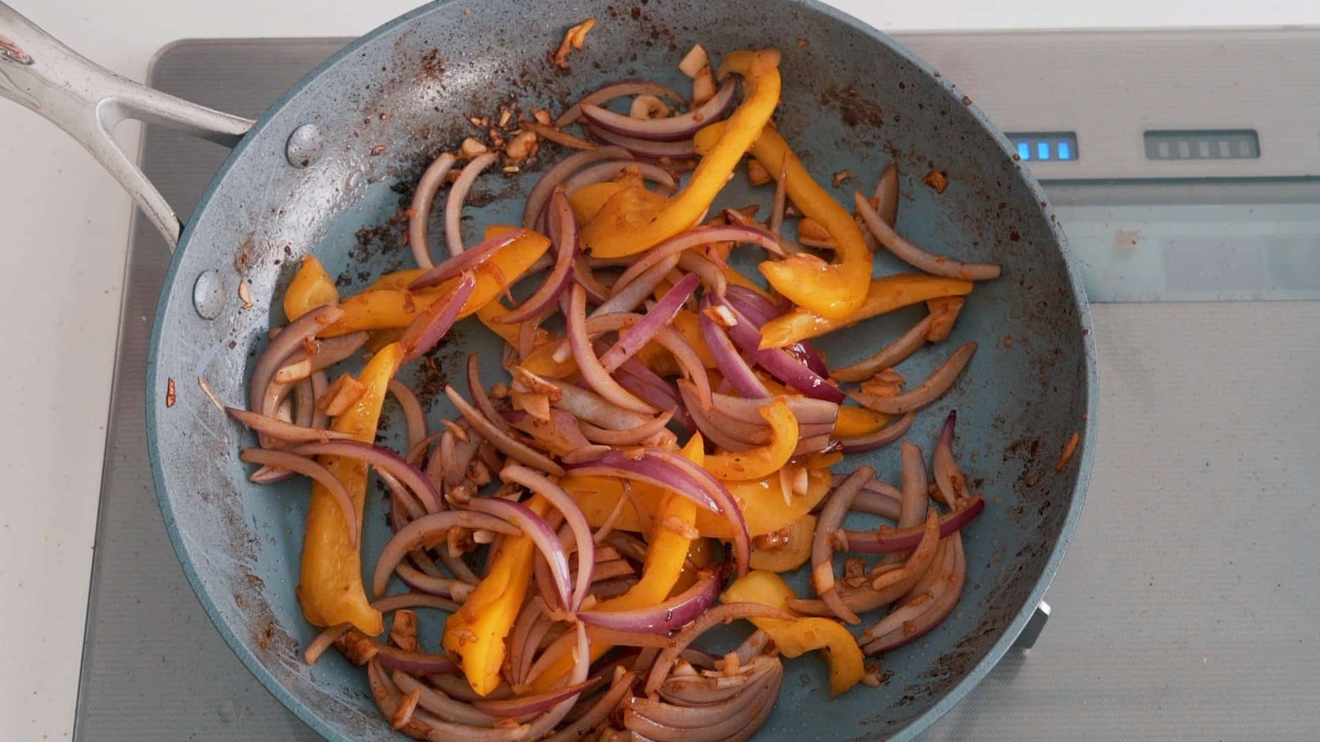 Stir-frying red onions and peppers for making Lomo Saltado.