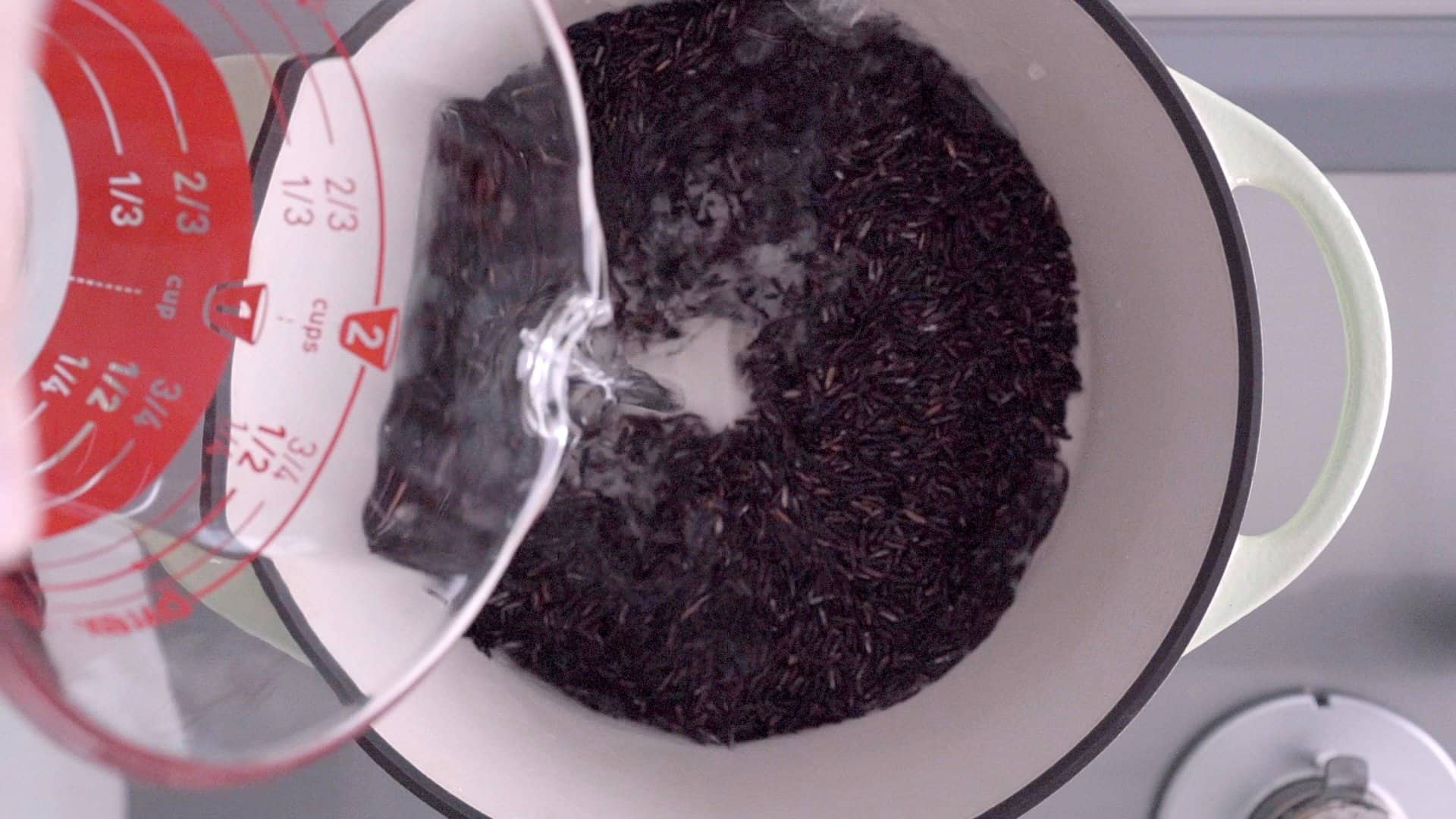 Adding water and Riceberry to a heavy bottomed pot.