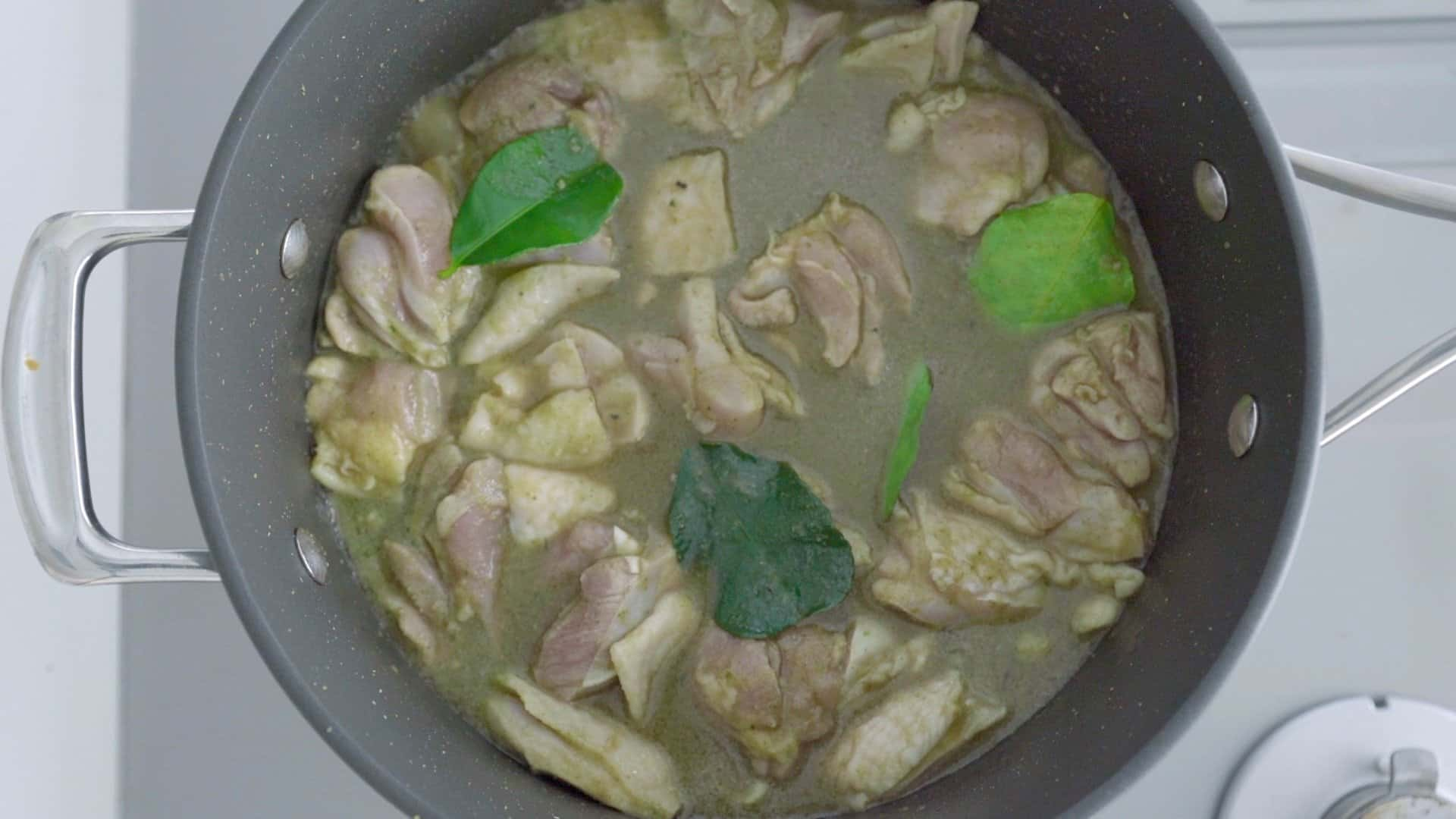 Simmering chicken and kaffir lime leaves in green curry.