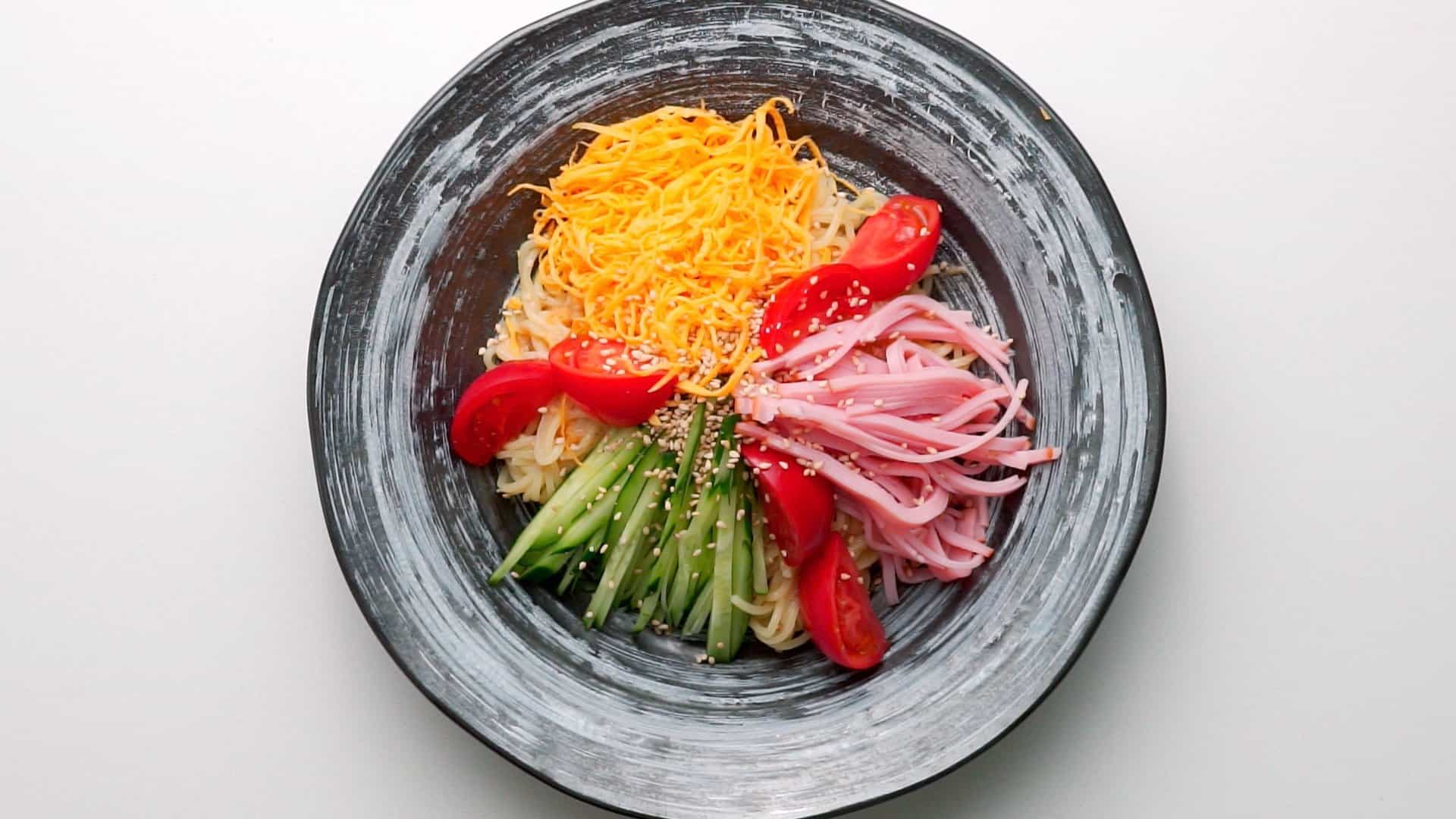 Plated Hiyashi Chuka with tomatoes, cucumbers, ham, Usuyaki Tamago, and chilled ramen noodles.