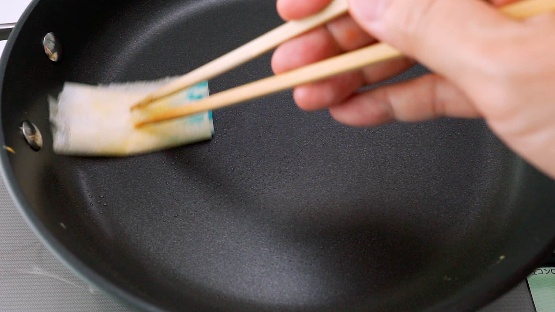 Wiping a non-stick frying pan with oiled paper towel to make Usuyaki Tamago