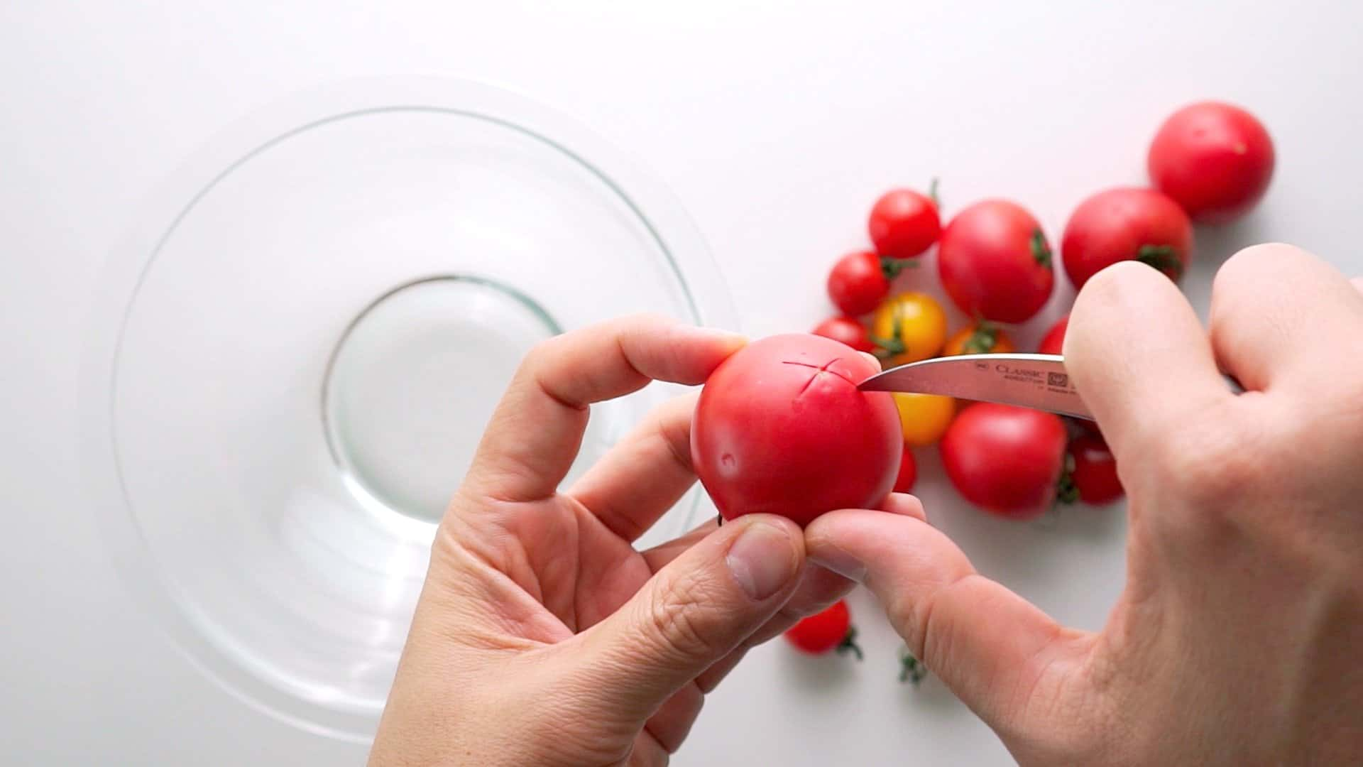 Score the tomato skin using a paring knife.