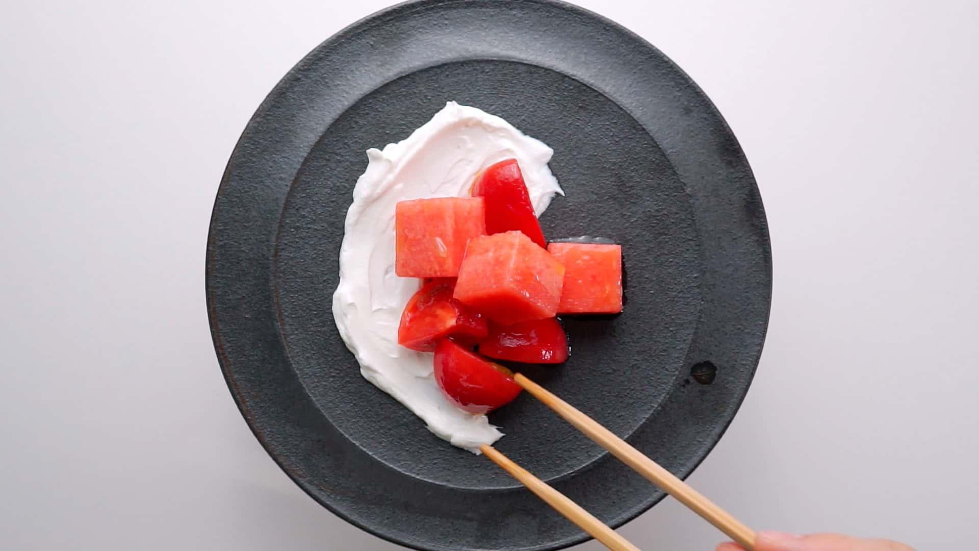 Plating watermelon and tomato salad.