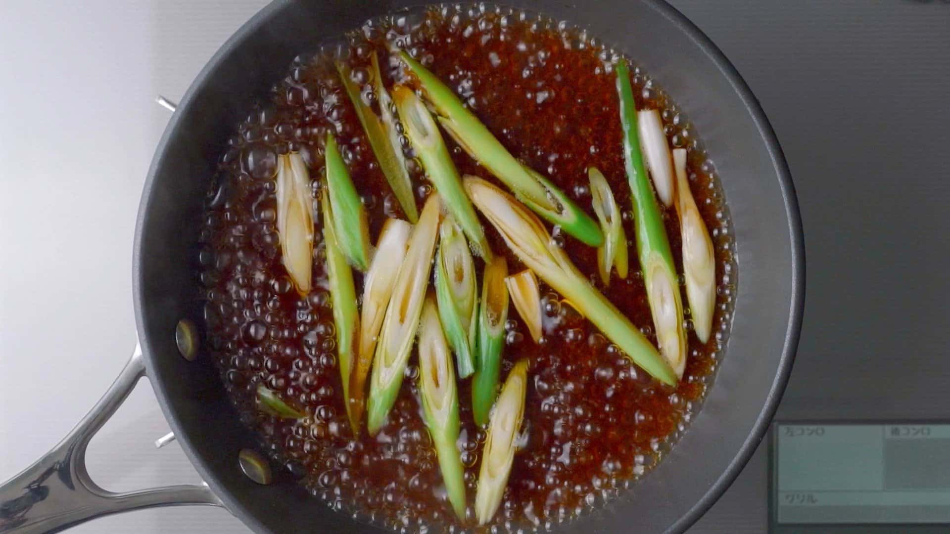 Scallions simmering in dashi stock for beef and egg rice bowl.