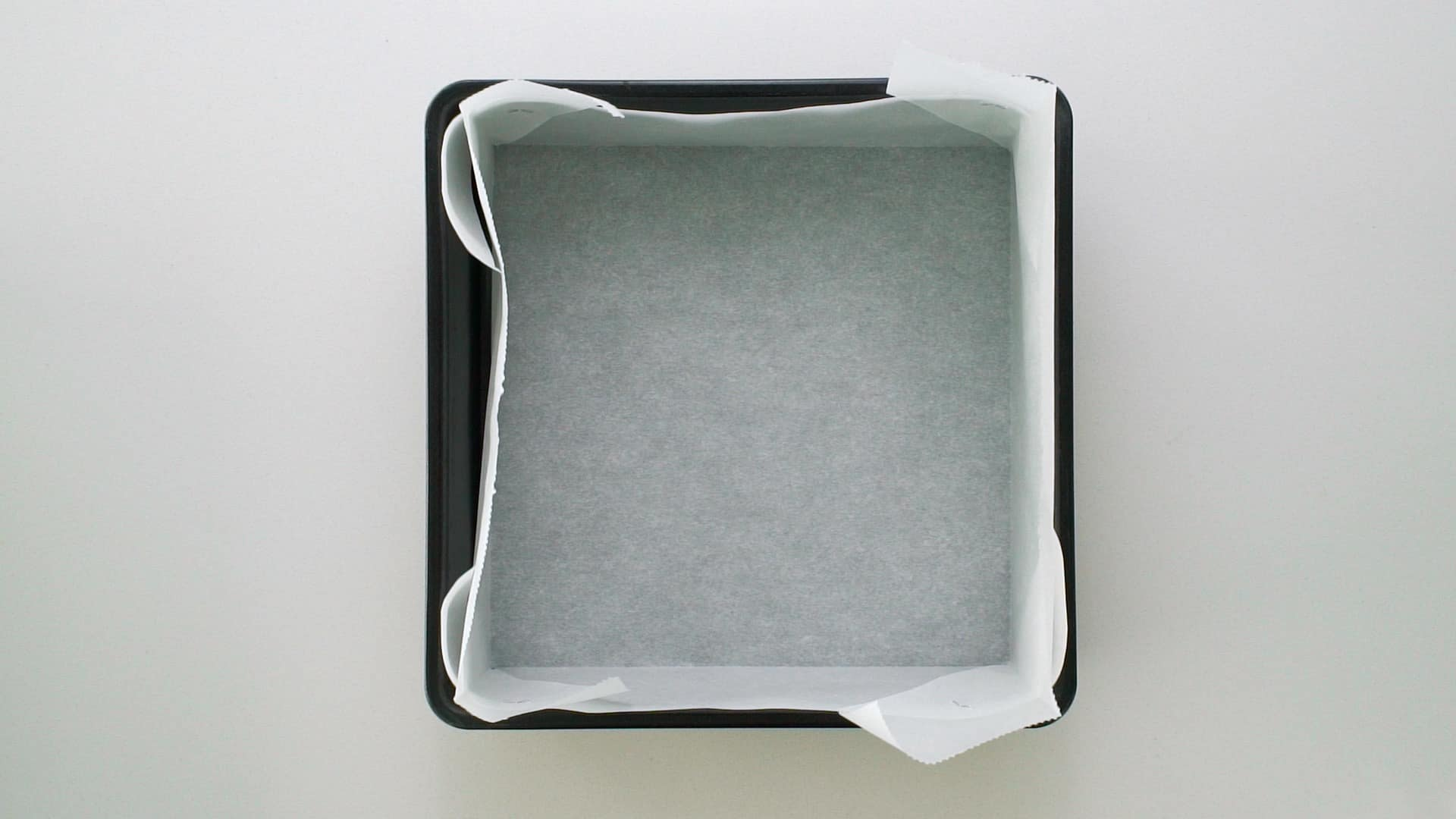 Square baking pan lined with parchment paper for making Datemaki.