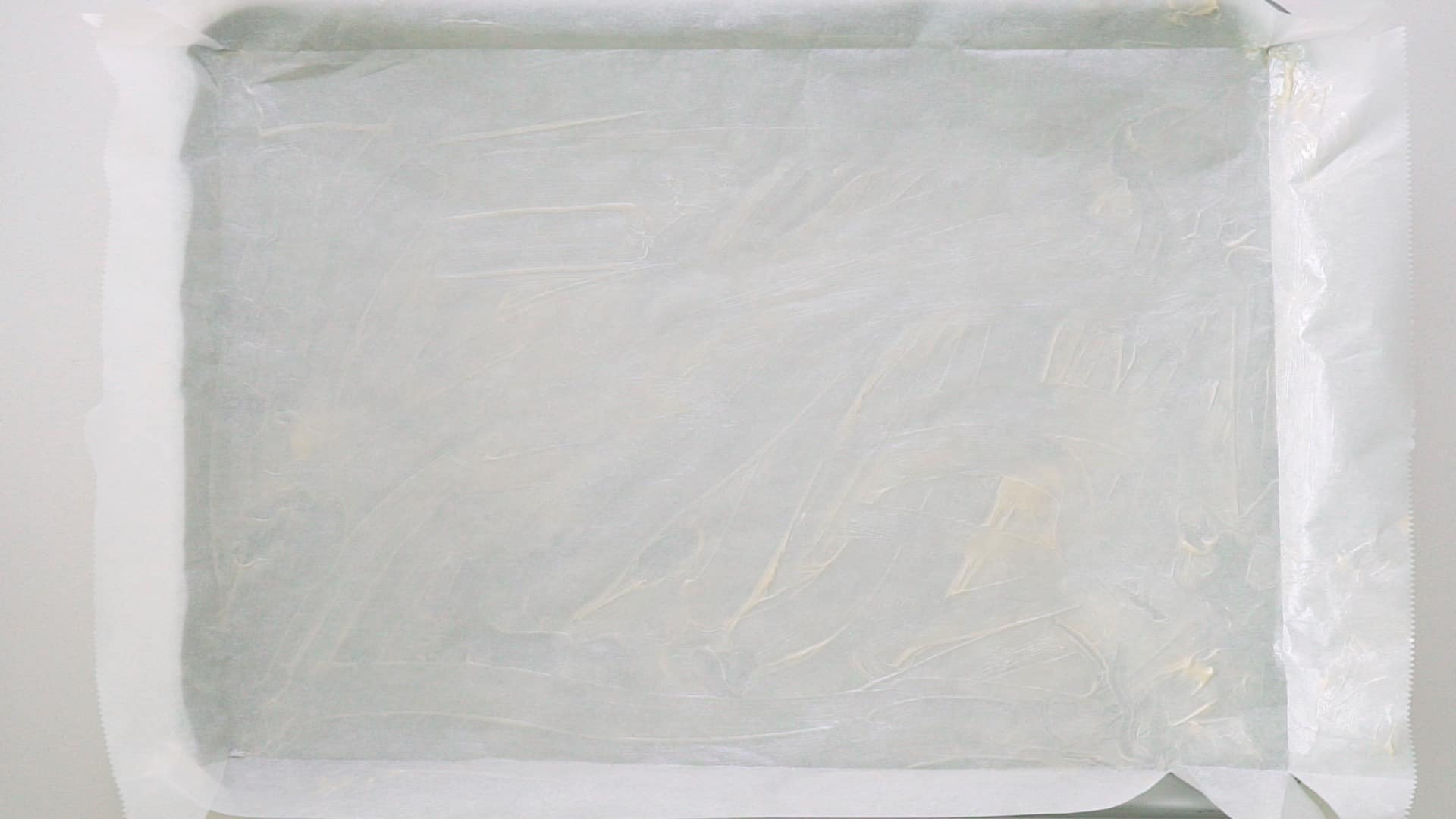 Buttered parchment paper in jelly roll pan.