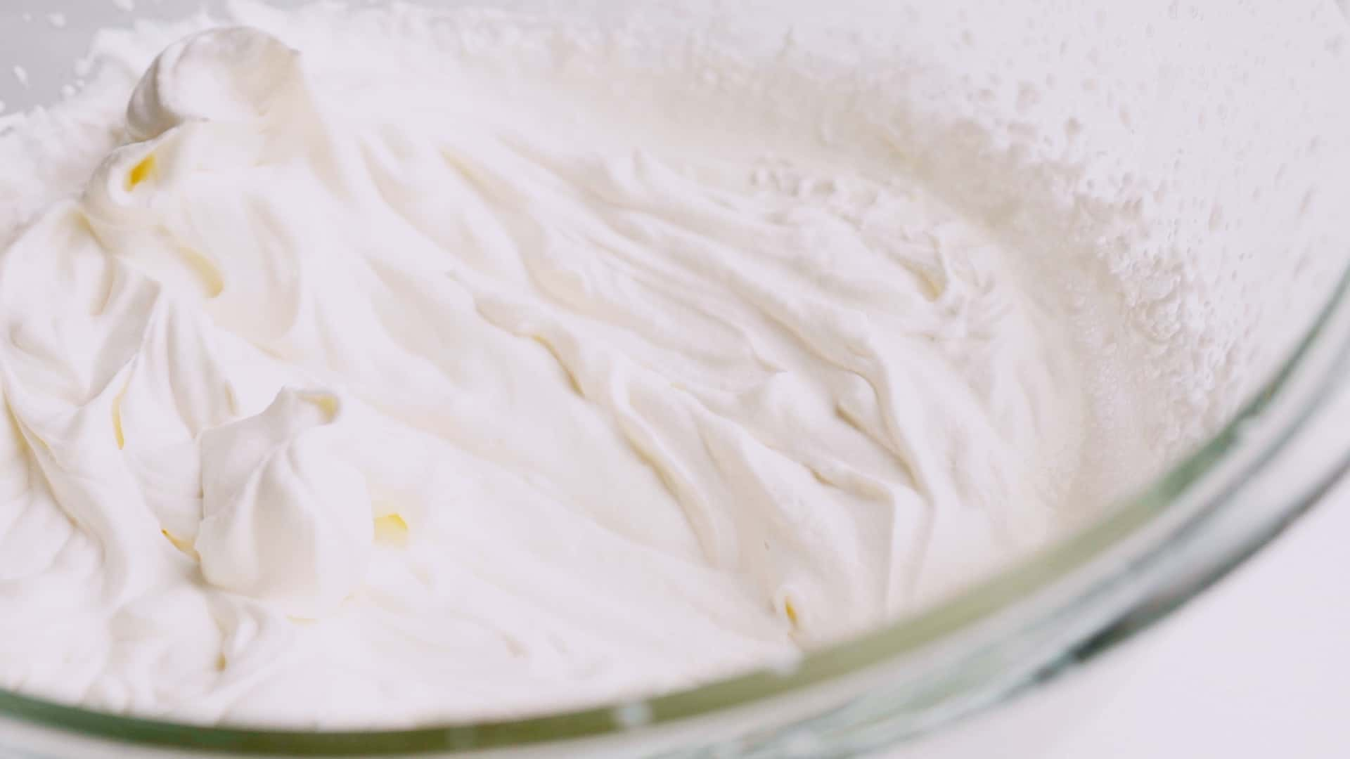 Whipped cream in glass bowl.