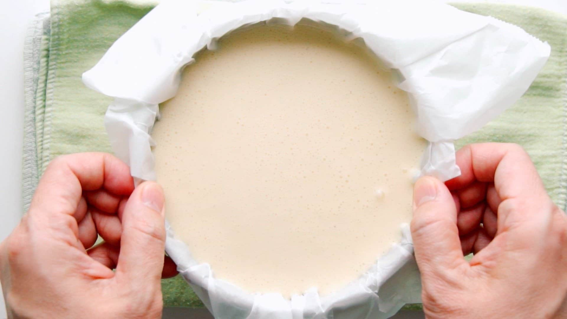 Removing bubbles from the cheesecake batter by dropping the pan on a flat surface.