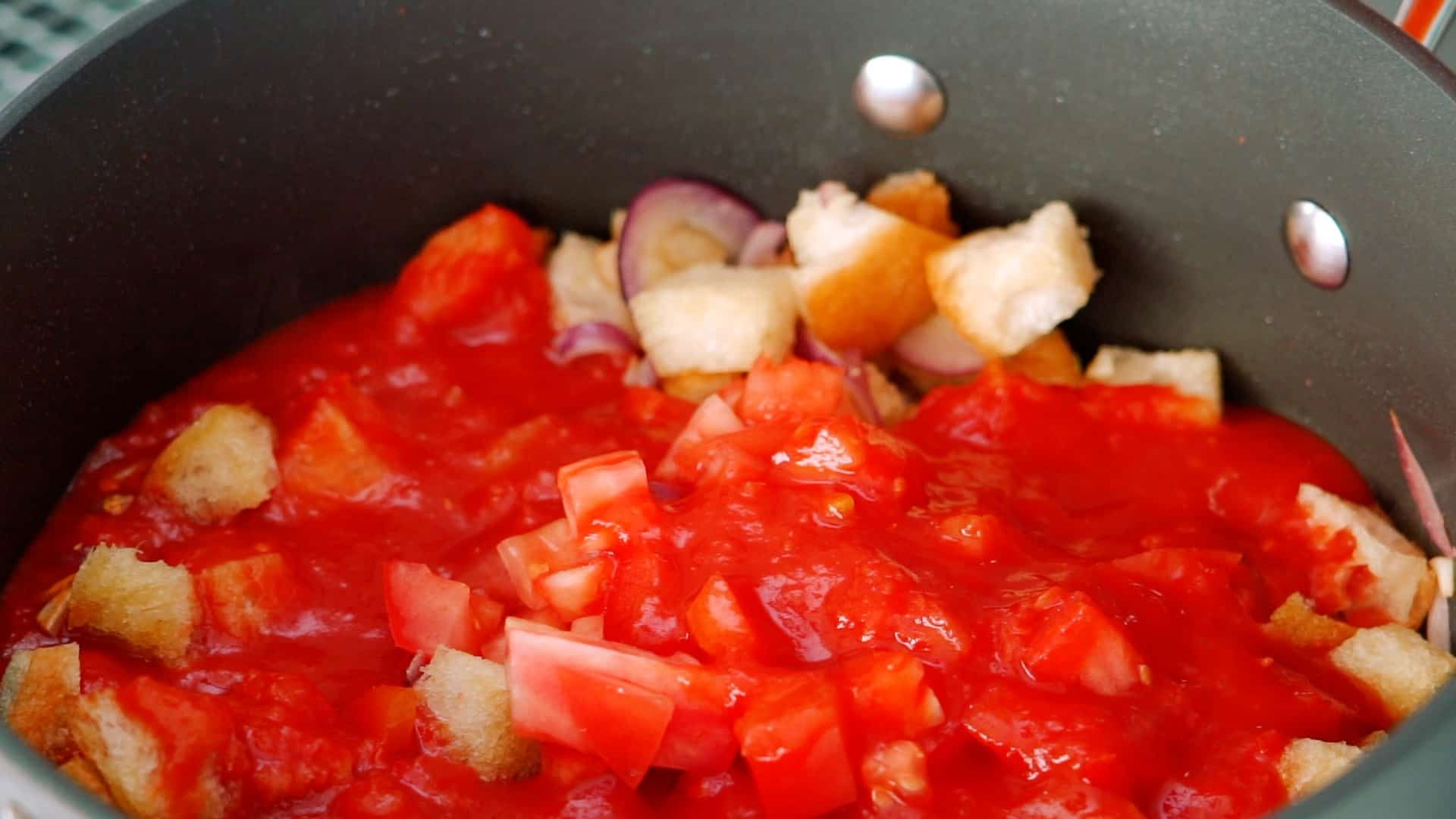 Adding tomatoes to sautéed bread.