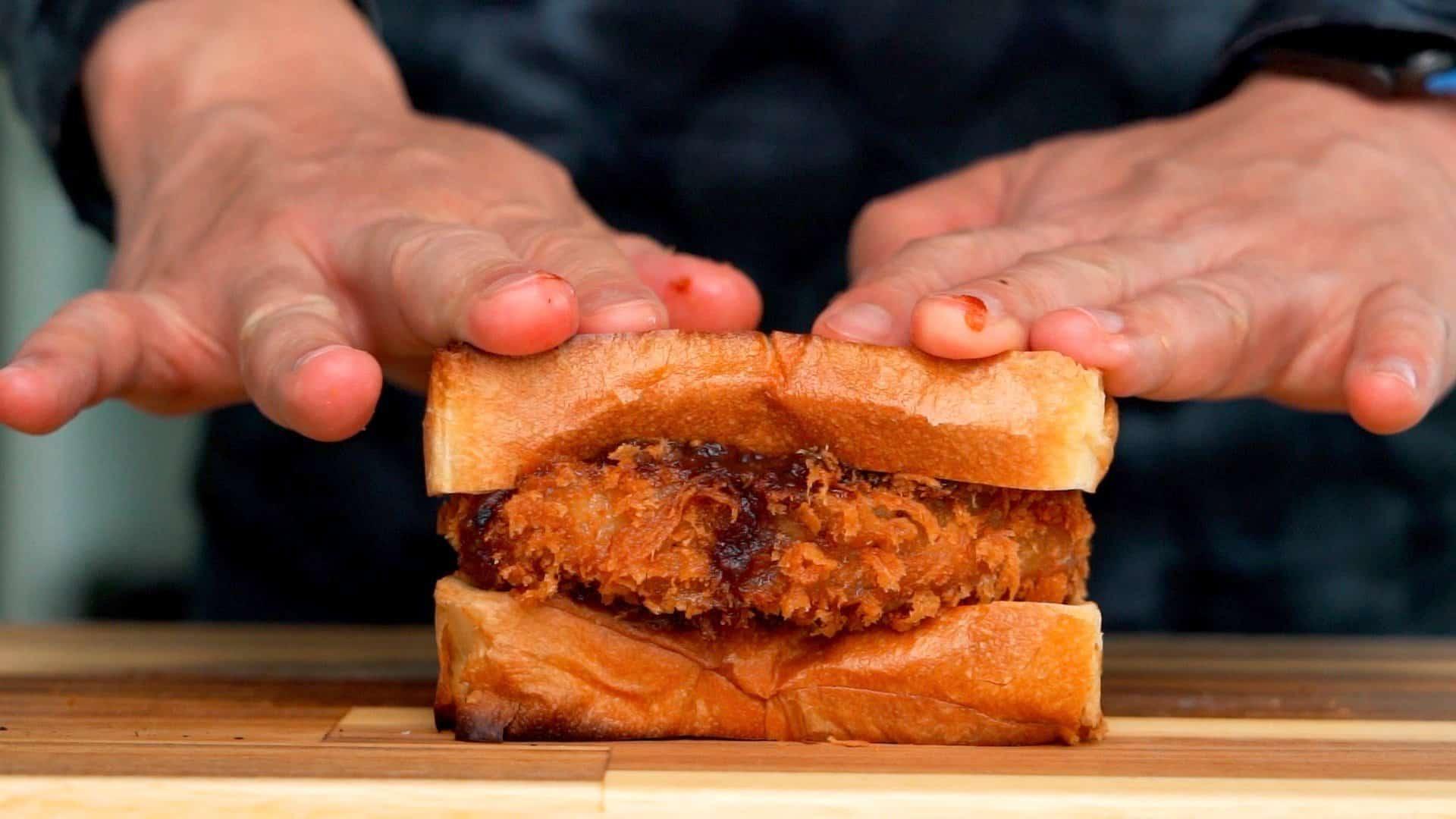 Wagyu Katsu between sandwich bread being pressed down.