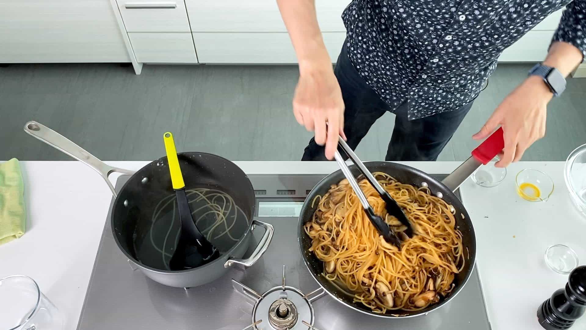 Tossing mushrooms, butter and soy sauce with pasta.