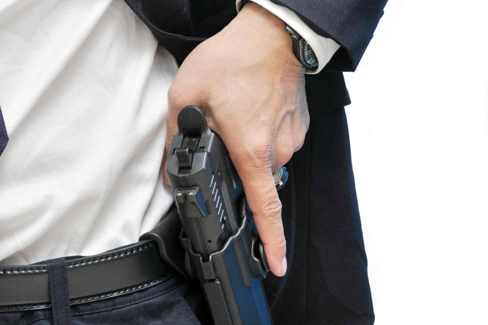 Armed bodyguard removing a gun from his holster
