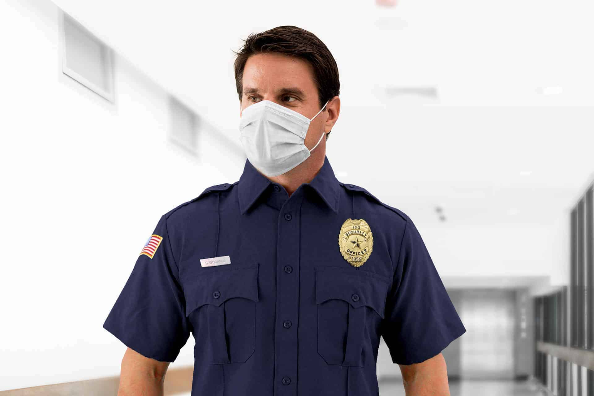 NYC security guard wearing a surgical mask standing in a hallway