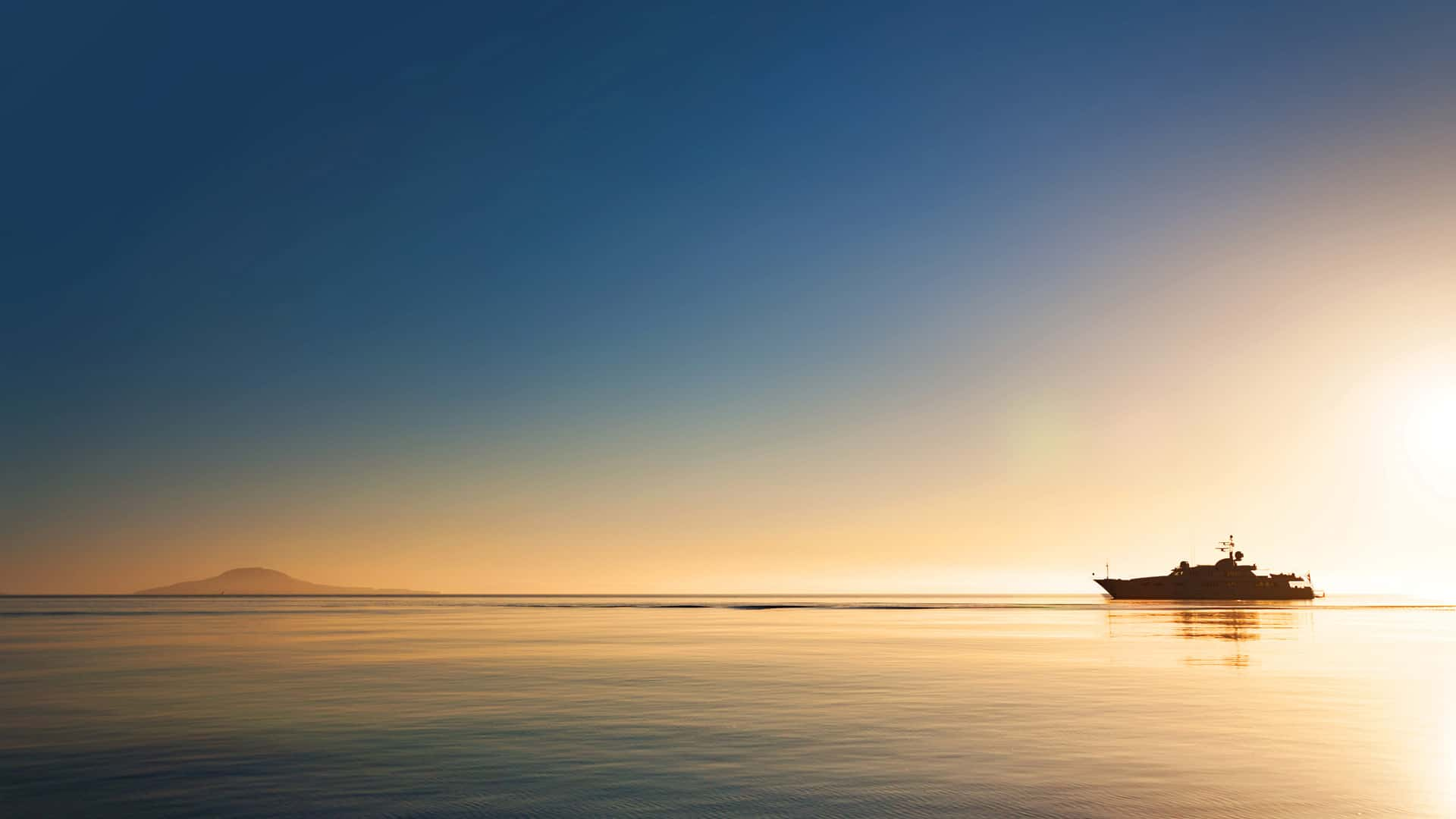 Superyacht cruising on a calm ocean at sunset