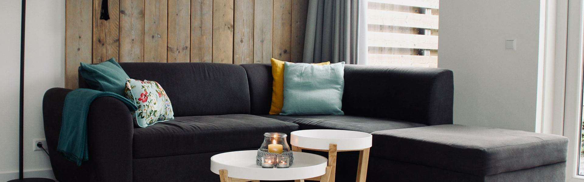 Living room consisting of black corner sofa against wooden tiled wall with small white coffee table with a candle