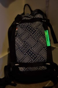 A backpack with a small glowstick on the zipper pull.