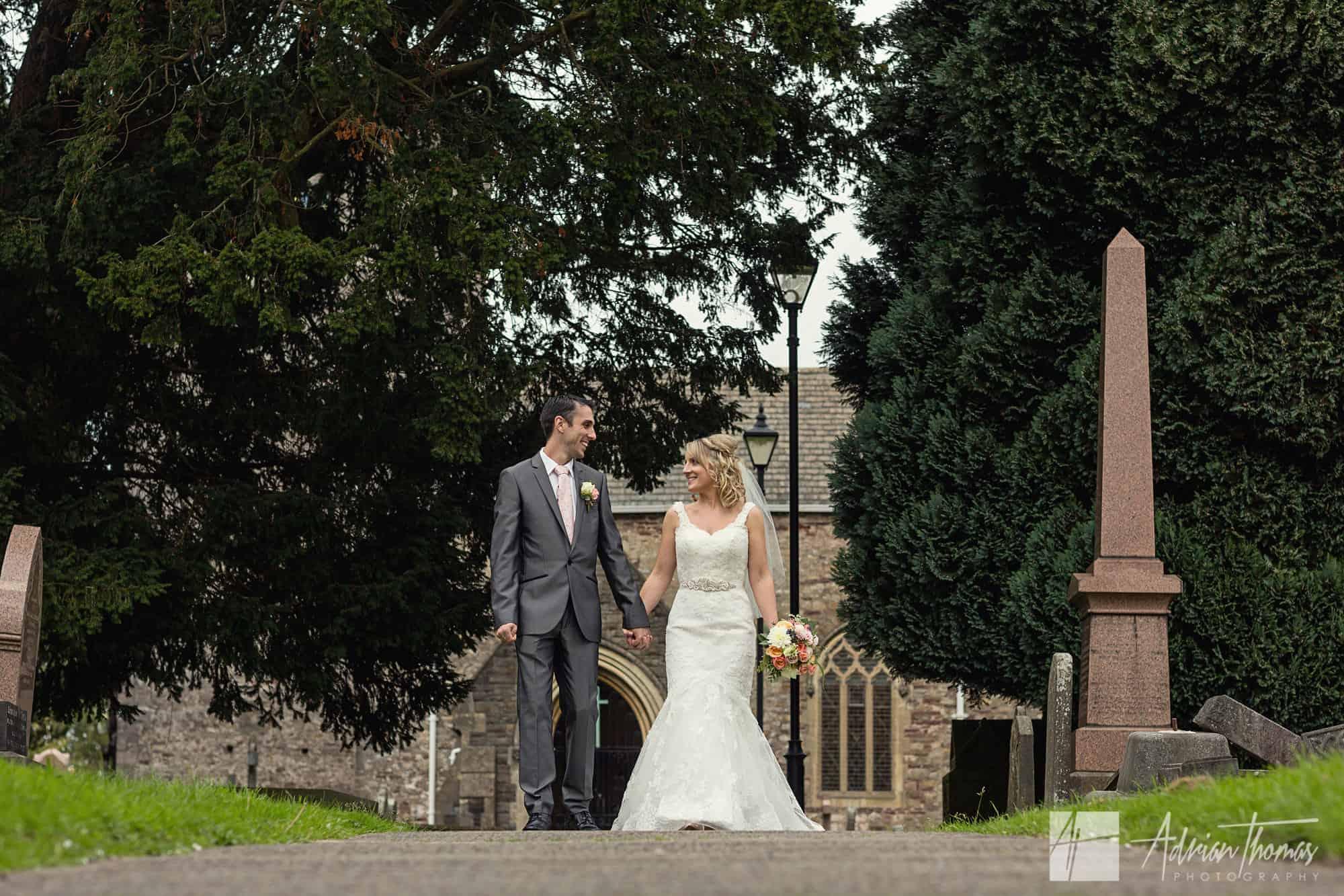 Wedding couple walking at St Basils Church in Bassaleg.