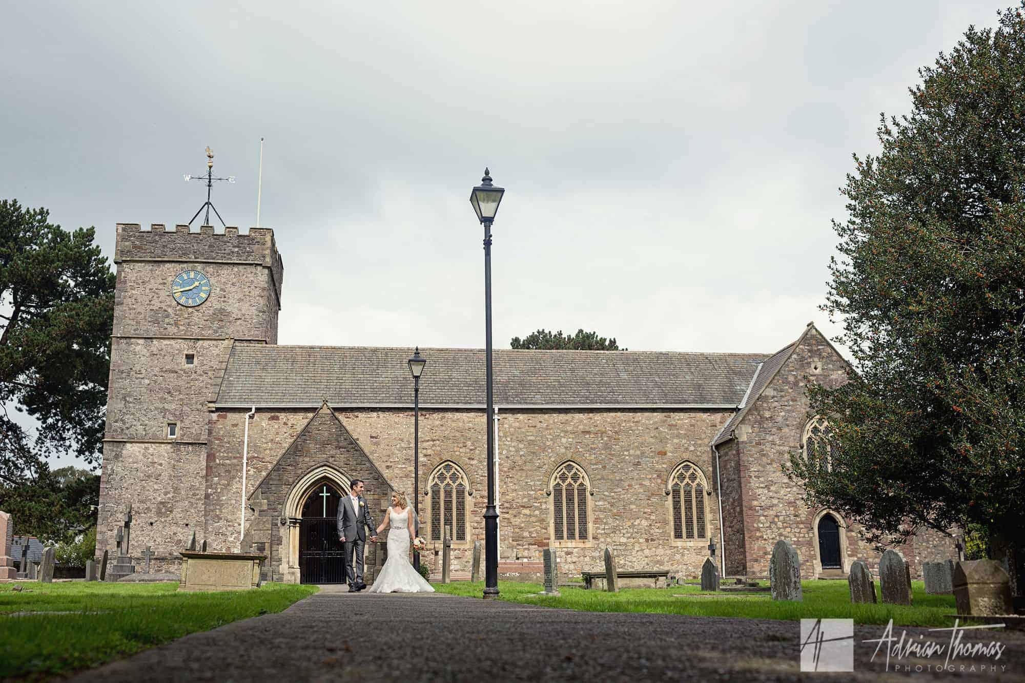 Bride and groom walking at St Basils Church near Cardiff.