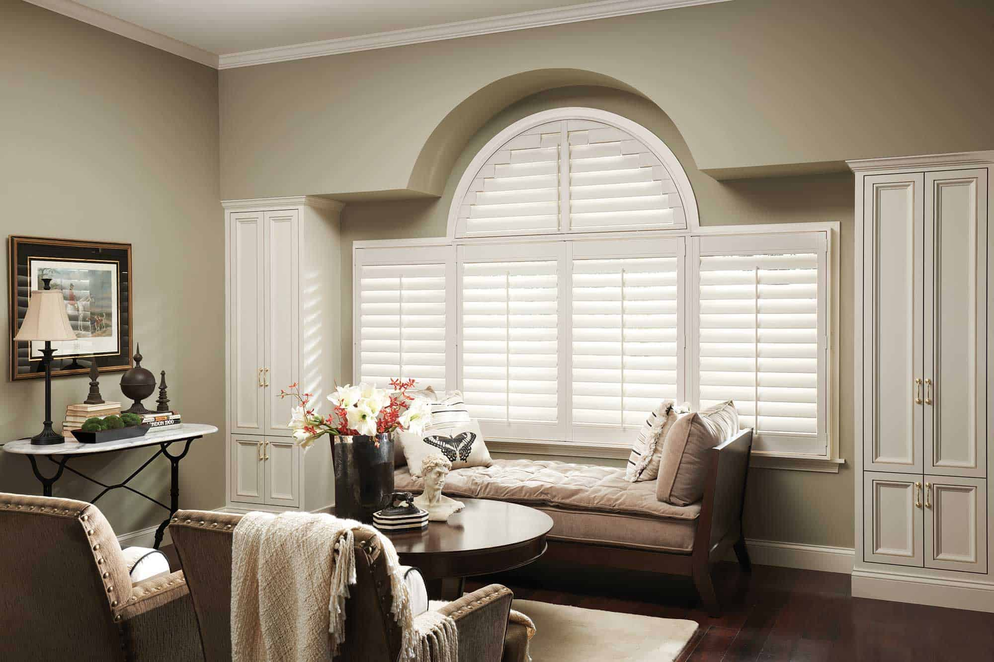 sitting room with arched panel shutters installed on windows