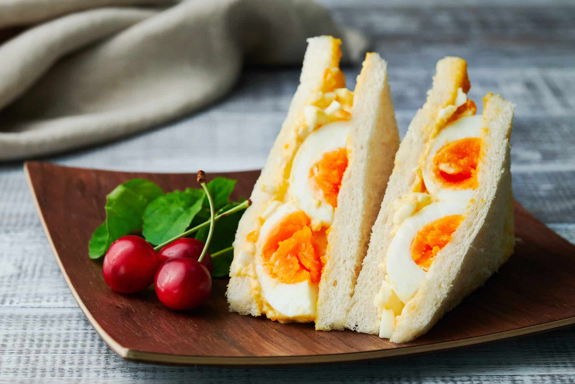 Japanese style egg sandwich including whole eggs on a wooden plate with cherries and arugula.