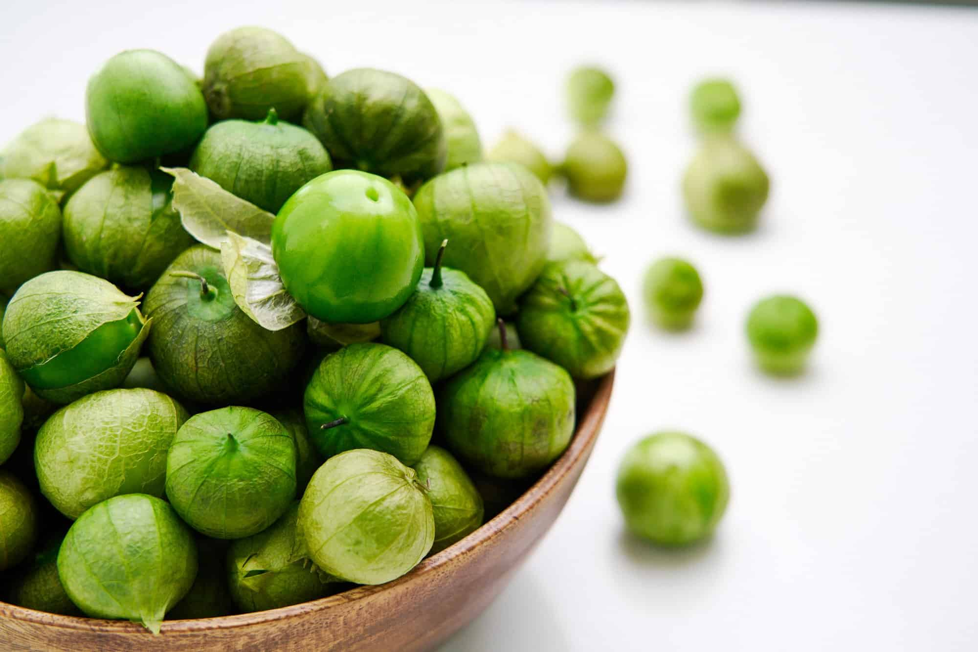 A wooden bowl overflowing with fresh tomatillos.